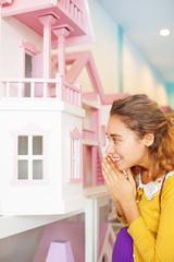 woman peeking inside a toy house
