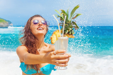 happy tourist woman holding a cocktail in her hands on a beach