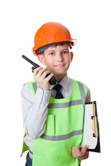 the young boy in hardhat and vest stands with portable radio