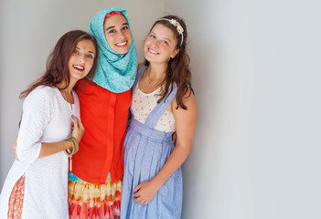 three friends of different religions standing happily together