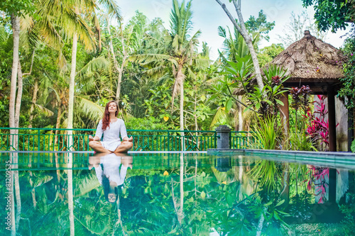 Woman meditation at gorgeous pool side of luxury tropical villa - 81209535