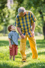 Grandfather and grandson talking in park