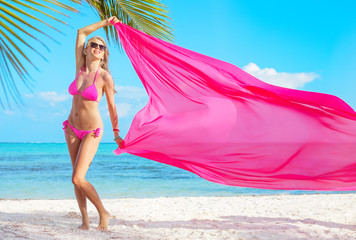 Woman in pink bikini holding pink fabric in wind on the beach