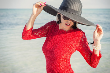 Stylish woman wearing black summer hat and red dress on beach