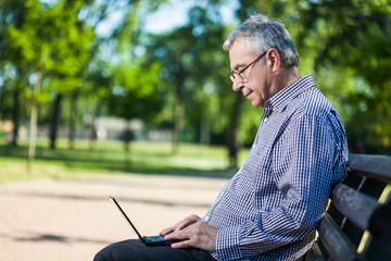 Senior man using laptop in park