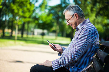 Senior man using digital tablet in park