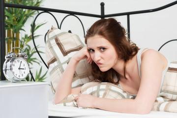 Junge Frau liegt schlaflos im Bett und ist genervt