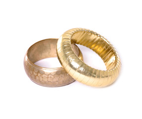 Two golden bangles on white