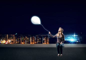 Young woman in casual holding balloon