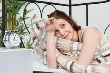 Junge Frau liegt im Bett und ist wach