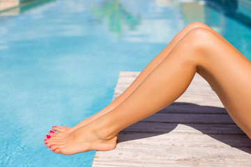 Beautiful women legs by the swimming pool