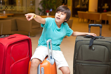 Boy with big suitcases is pointing you travel