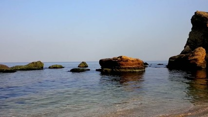 Black sea, surf, a large stone and blue water