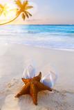 Art flip flops and starfish on a tropical beach