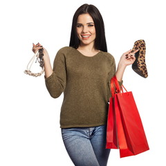 Smiling woman holding a shoe, a necklace, and red shopping bags
