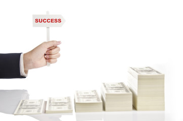 holding success sign over growing money