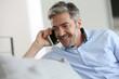 Leinwanddruck Bild - Mature man sitting in sofa and talking on phone