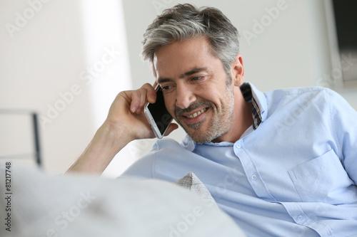 Leinwanddruck Bild Mature man sitting in sofa and talking on phone