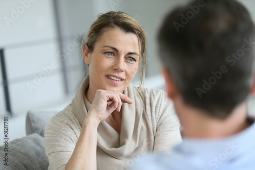 Couple at home sitting in sofa and having a talk - 81217781