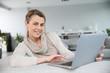 Leinwandbild Motiv Mature woman sitting in sofa an websurfing with laptop