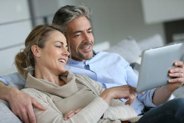 Mature couple relaxing in sofa and using digital tablet