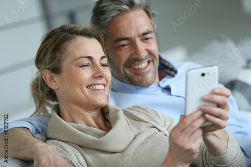 Leinwandbild Motiv Mature coupel sittign in sofa and using smartphone