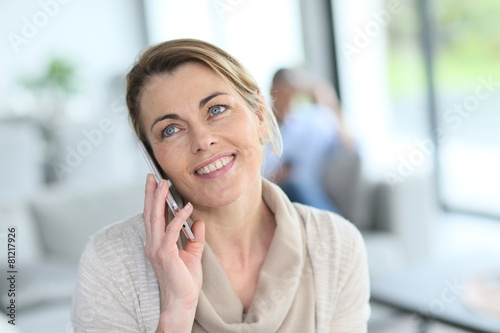 Portrait of mature blond woman talking on phone - 81217926