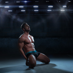 Sexy Thoughtful Athletic Man Kneeling on the Floor