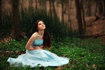 Romantic young girl in a long blue dress, in twilight forest