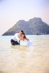 bride and groom embrace half in shallow water