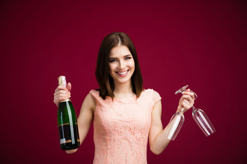 Happy woman holding two glass and bottle of champagne