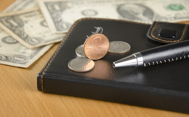 Notebook, US coins and office supply on the desk