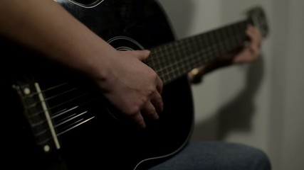 Woman playing a black guitar.