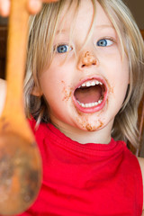 Shouting child holding chocolate covered spoon after baking