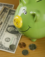 Green piggy bank and US coins isolated