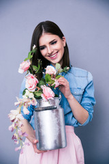 Smiling young cute woman holding flowers