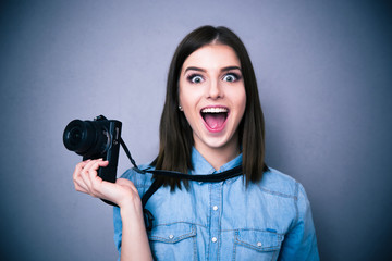 Amazed young pretty woman holding camera