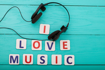 I love music.Headphones and letters on wooden background