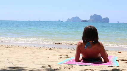 young brunette girl sitting on the beach