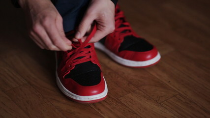 guy tying the laces on red sneakers