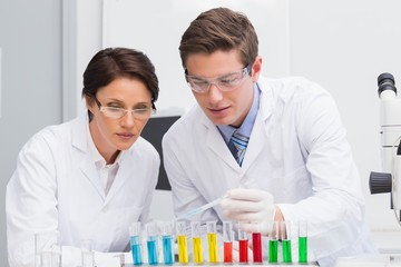 Scientists looking attentively at test tube