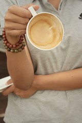 Woman holding a cup of coffee at the cafe