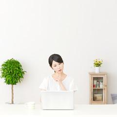 パソコンの前に座って考える女性
