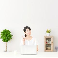 パソコンの前に座ってひらめく女性