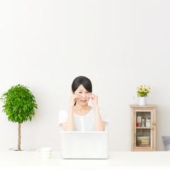 パソコンの前に座って泣く女性
