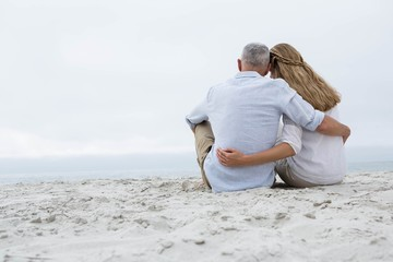Happy couple sitting on the sand and looking at the sea