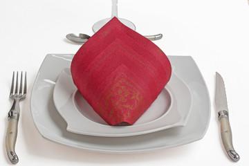 Pliage de serviette papier grenat en cornet sur assiette blanche