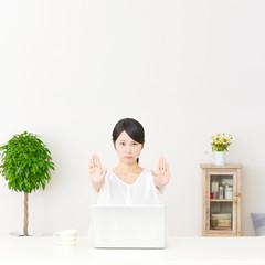 パソコンの前に座って制止する女性