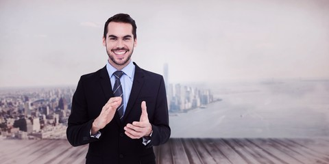 Composite image of happy businessman standing and applauding