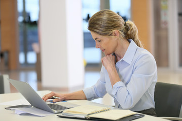Businesswoman working in office on laptop